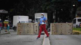 Una mujer camina entre bloques de concreto que obstaculizan la entrada a la principal avenida de El Paraíso, un vecindario de Caracas