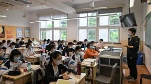 Students wear face masks in a classroom as school reopens in Shanghai