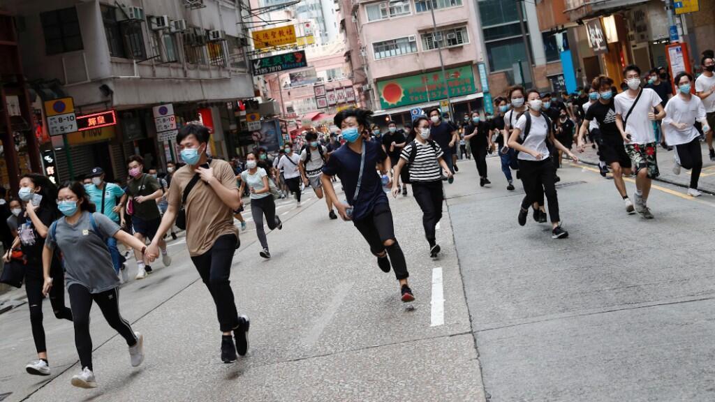 Los manifestantes corren huyendo de los gases lacrimógenos de la Policía. 24 de mayo de 2020.