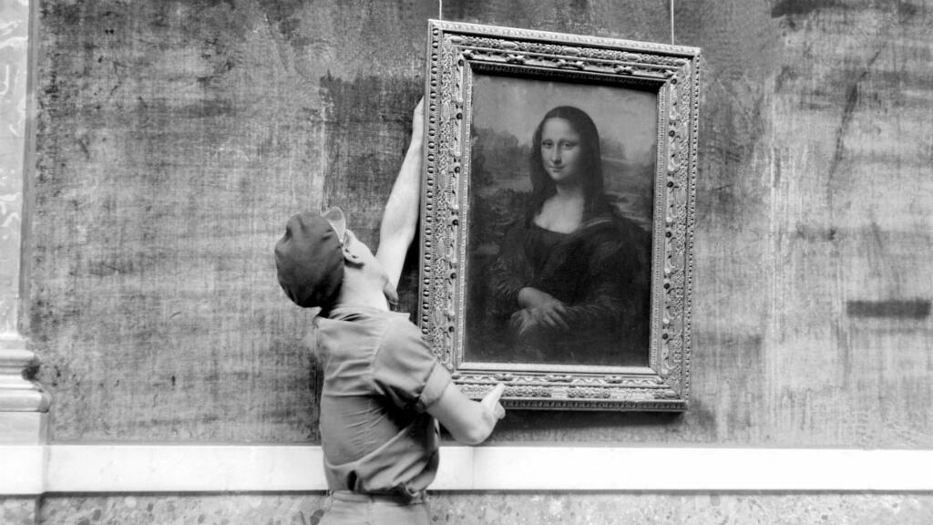 En esta imagen de archivo, tomada el 6 de octubre de 1947, un empleado del museo del Louvre cuelga el famoso retrato de la Mona Lisa del artista italiano Leonardo da Vinci.