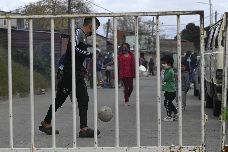 Archivo-Niños juegan fútbol detrás de una barrera que aísla al barrio popular bonaerense Villa Azul luego de que el gobierno de la provincia detectó al menos 53 personas contagiadas de covid-19 en Quilmes, provincia de Buenos Aires, Argentina, el 25 de mayo de 2020