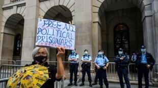 Une militante pro-démocratie brandit une pancarte police appelant à la libération des prisonniers politiques devant le tribunal de Hong Kong où comparaît Jimmy Lai le 1er février 2021