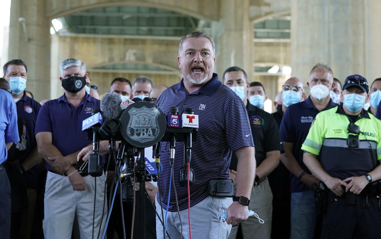El presidente de la Asociación de Beneficencia de la Policía de Nueva York, Mike O'Meara, y representantes de otros sindicatos de policía de Nueva York y de la policía celebran una reunión de prensa en el estacionamiento del estadio Icahn el 9 de junio.