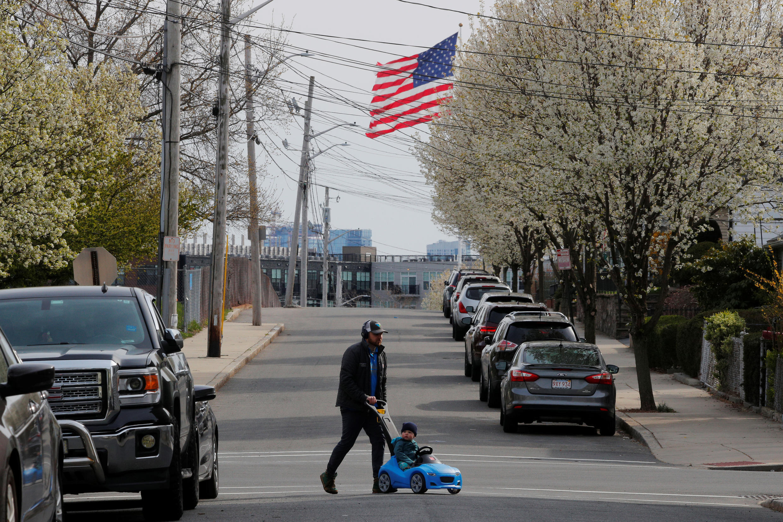رجل وطفل يعبران الشارع وسط تفشي فيروس كورونا في تشيلسي، ماساتشوستس ، الولايات المتحدة، 17 أبريل/ نيسان 2020