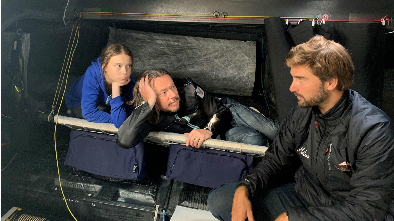 """Greta Thunberg junto a su padre Svante y el capitán Boris Hermann conversan en Plymouth, Reino Unido, a bordo del velero """"Malizia II"""" que los llevará a Nueva York . Agosto 12 de 2019."""