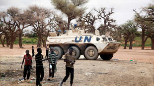 Sudanese boys walking past a UNAMID tank in Kutum, Darfur.