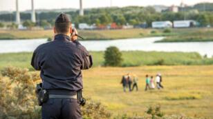 Un gendarme français filmant des migrants tentant de s'approcher du site d'Eurotunnel, à Coquelles, près de Calais, le 31 juillet 2015.