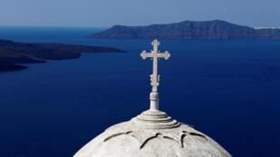 كنيسة أرثوذكسية يونانية مبنية على حافة فوهة بركان في جزيرة سانتوريني، 15 مارس/آذار 2012.