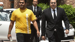 Pakistan cricketer Umar Akmal (left) with his lawyer in Lahore