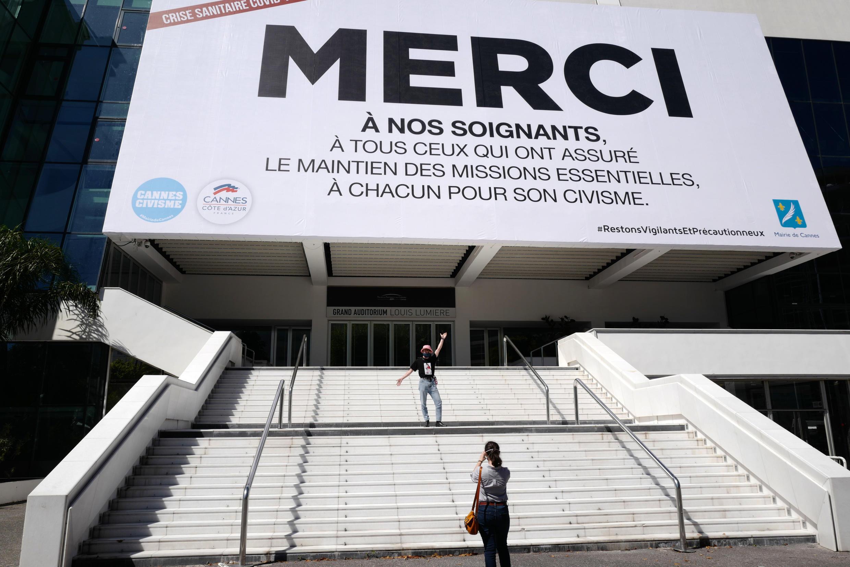 """امرأة تلتقط صورة أمام ملصق عملاق كتب عليه """"شكرًا لطاقمنا الطبي"""" بالقرب من قصر المهرجانات في مدينة كان الفرنسية في الريفيرا، جنوب فرنسا، في 12 مايو/أيار 2020."""