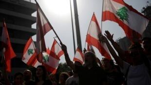 Des manifestants arborent des drapeaux nationaux lors de manifestations antigouvernementales à Beyrouth, au Liban, le 6 novembre 2019.