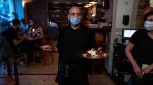 صورة تعود إلى 15 أيار/مايو 2020 لنادل يضع كمامة خلال عمله في مطعم في برلين