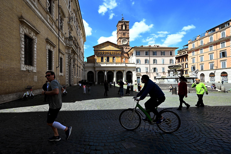 Ciudadanos italianos salen a la plaza Santa María de Trastevere, en Rome, el 3 de mayo de 2020.