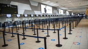 Marcas en el suelo señalizan donde colocarse al hacer fila para facturar en el aeropuerto Jorge Chávez de Lima, que comenzó a operar pero permanece casi vacío