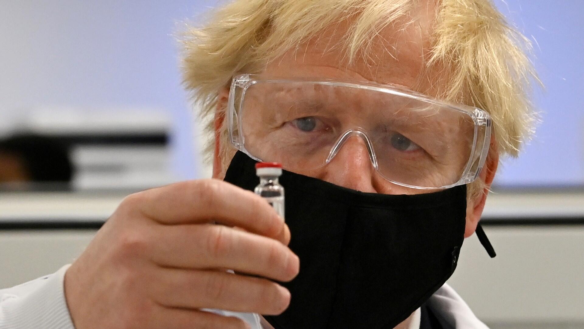 El primer ministro británico Boris Johnson posa con la vacuna candidata de la Universidad de Oxford / AstraZeneca, conocida como AZD1222, en la planta de fabricación farmacéutica de Wockhardt en Wrexham, Gales, Reino Unido, el 30 de noviembre de 2020.
