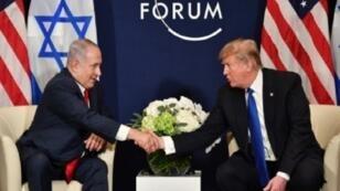 ترامب مصافحا نتانياهو خلال لقائهما على هامش منتدى دافوس في 25 كانون الثاني/يناير.