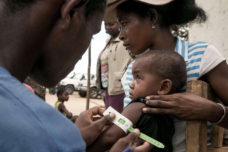 عنصر في منظمة غير حكومية يفحص طفلا لرصد أي حالات سوء تغذية في جنوب مدغشقر بتاريخ 14 كانون الأول/ديسمبر 2018