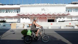 Una mujer monta una bicicleta frente al Palazzo del Cinema en el 76o Festival de Cine de Venecia en Venecia, Italia, el 27 de agosto de 2019.