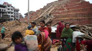 Des Népalais passent devant des décombres dans le centre de Katmandou, dimanche 26 avril.
