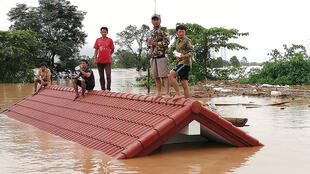 Des villageois sur le toit d'une maison submergée par les eaux, le 25 juillet, dans la province d'Attapeu, au Laos.