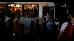 Venezoalnos se suben a uno de los pocos autobuses disponibles durante el apagón en Caracas, Venezuela, el 7 de marzo de 2019.
