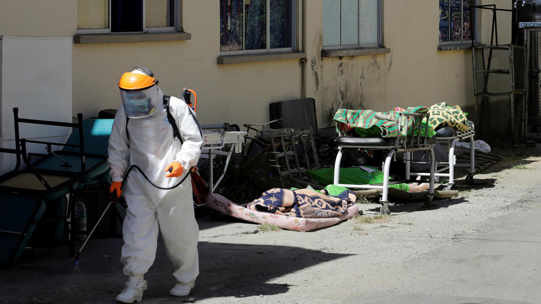 Un trabajador de la salud rocía desinfectante cerca de varios cuerpos, que los agentes de la Fuerza Especial contra el Crimen transportaron al Hospital de Clínicas, en La Paz, Bolivia, el 27 de julio de 2020.