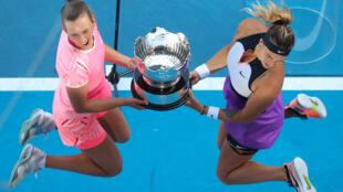 Elise Mertens et Aryna Sabalenka sautent de joie après leur victoire en finale du double dames de l'Open d'Australie le 19 février 2021 au Melbourne Park