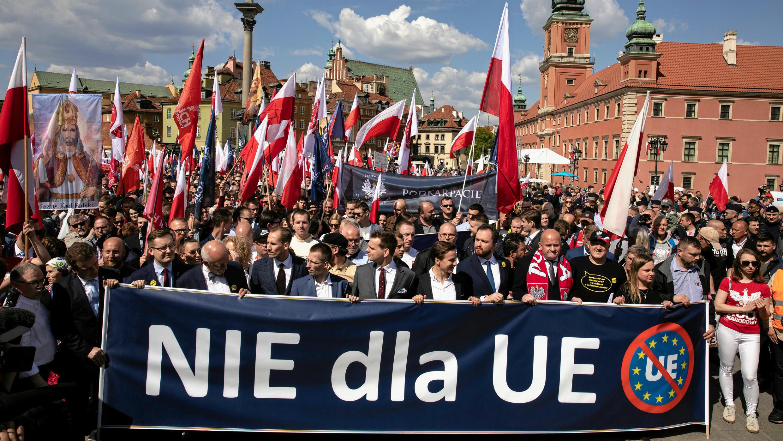 """Manifestantes con una pancarta  """"No por la UE"""" en una marcha organizada por grupos de extrema derecha contra la Unión Europea  mientras mandatarios de Europa Central y Oriental se reunían en la ciudad para una cumbre, en Varsovia, Polonia, 1 de mayo de 2019."""