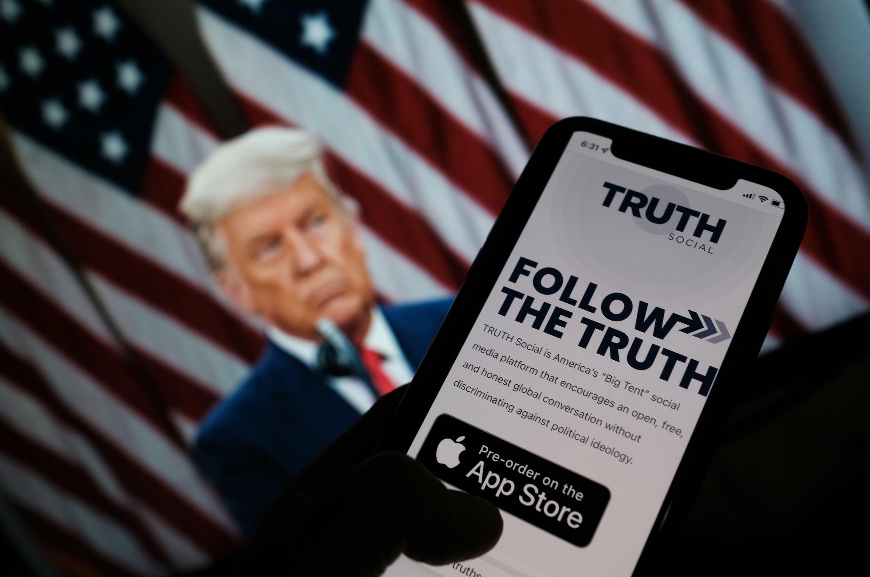 """Una persona muestra la aplicación """"Truth social"""" en su teléfono, frente a un fondo de pantalla de Donald Trump, en Los Ángeles el 20 octubre de 2021"""