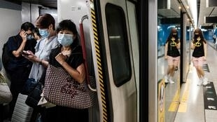 """Commuters wear face masks on a metro train in Hong Kong. The city's leader says coronavirus is running """"out of control"""" afater a daily record number of new cases"""