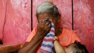 Dolores Morales López, abuela de la migrante guatemalteca Ledy Pérez, reacciona mientras carga a su bisnieta Marisol después de ver un video de Ledy en su casa en la comunidad de Santa Amelia.