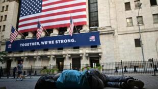 Un homme allongé sur un banc face au New York Stock Exchange (NYSE) à Wall Street (New York), le 13 juillet 2020