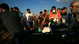 Des secouristes palestiniens s'occupent d'une personne blessée par les forces de sécurité israéliennes à la frontière entre Israël et la bande de Gaza, le 12 octobre 2018.