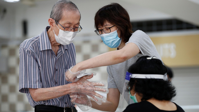Un pariente ayuda a un votante a ponerse guantes de plástico, como parte de las medidas preventivas contra el brote de la enfermedad del coronavirus (COVID-19), en un colegio electoral durante las elecciones generales en Singapur el 10 de julio de 2020.