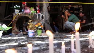 Des hommes se recueillent sur les lieux de l'attentat qui a coûté la vie à 300 personnes le 3 juillet dernier à Bagdad.