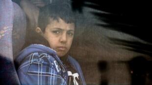Un enfant migrant regarde par la fenêtre d'un bus, alors que les garde-côtes ont intercepté des migrants tentant de se rendre en Grèce.