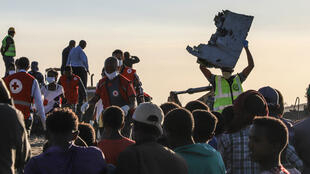 Un homme brandit, dimanche 10mars, un débris du Boeing737MAX qui s'est écrasé en Éthiopie.