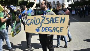 """Un manifestant porte une pancarte """"Gaïd Salah dégage"""", lors d'une manifestation contre l'ex-président, Abdelaziz Bouteflika, le 29 mars 2019."""