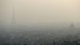A file picture dated March 11, 2014 shows the Eiffel Tower and Paris roofs through a haze of pollution