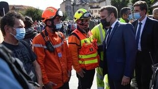 French President Emmanuel Macron (R) meets with rescuers during a visit to Tende, in the Vallee de la Roya, some 50km north-east of Nice, southeastern France, on October 7, 2020, after storms and flooding caused widespread damage in the Alpes-Maritimes area.