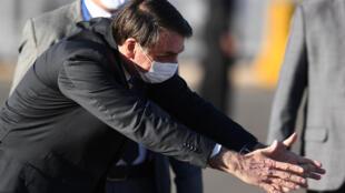 El presidente de Brasil, Jair Bolsonaro, le extiende los brazos a una niña en una ceremonia en el Palacio Alvorada de Brasilia el 12 de mayo de 2020