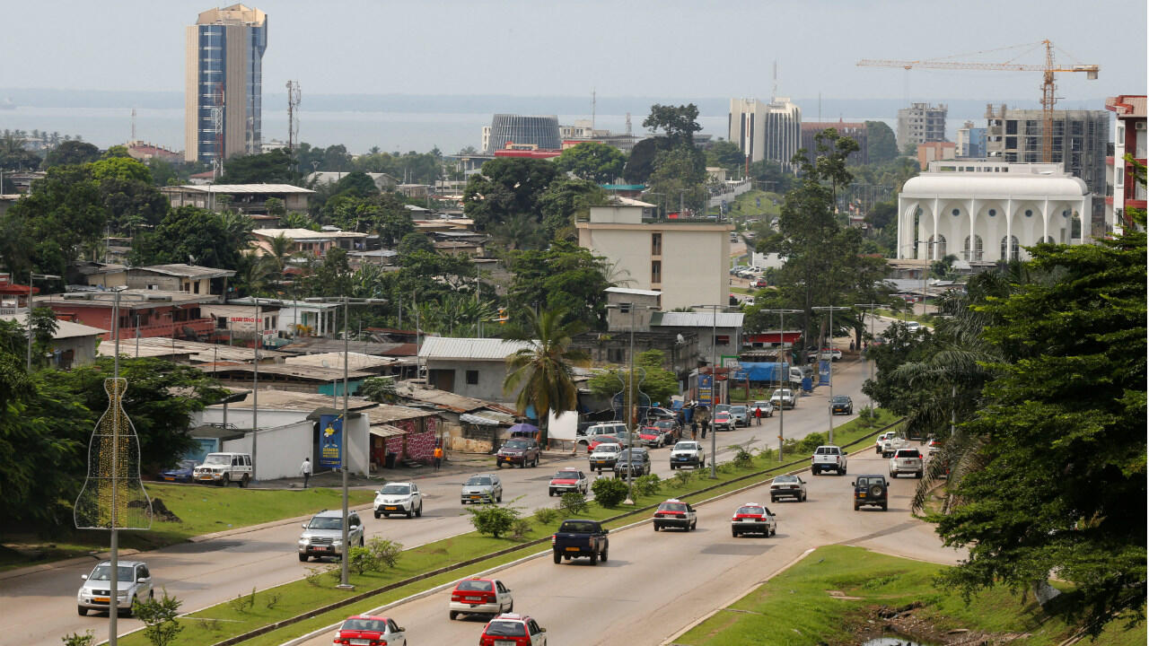 Cars drive down a highway beneath the skyline of Libreville, Gabon's capital, on January 16, 2017.