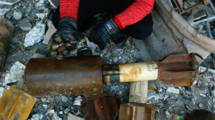 Un Syrien montre les restes d'une roquette tirée dans la ville de Douma.
