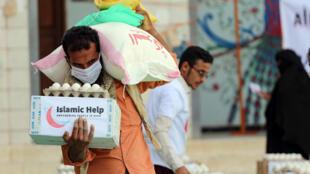 رجل يضع كمامة لدى تلقيه مساعدات إنسانية في تعز بتاريخ 8 أيار/مايو 2020