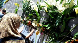 Une femme se recueille près d'un camion transportant les corps de victimes récemment identifiées du massacre de Srebrenica, le 9 juillet 2017.