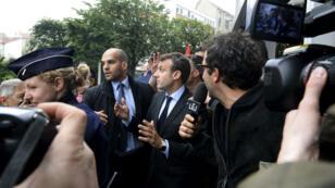 Emmanuel Macron tente de fendre la foule de manifestants, massée devant un bureau de poste de Montreuil, lundi 6 juin.