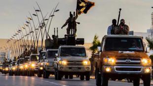 Des militants du mouvement terroriste de l'État islamique roulent à travers la ville de Syrte, en Syrie.