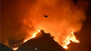 A firefighting helicopter flies over the Getty Fire as it burns in the hills west of the 405 freeway in the hills of West Los Angeles, California, on October 28, 2019.