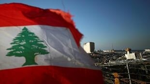 Una bandera libanesa ante el área portuaria devastada por la explosión en Beirut, Líbano, el 17 de agosto de 2020.