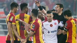 لاعبون من الوداد البيضاوي المغربي والترجي التونسي يحيطون بالحكم المصري جهاد جريشة للاعتراض على أحد قرارته خلال ذهاب الدور النهائي لمسابقة دوري أبطال أفريقيا، في 24 أيار/مايو 2019.